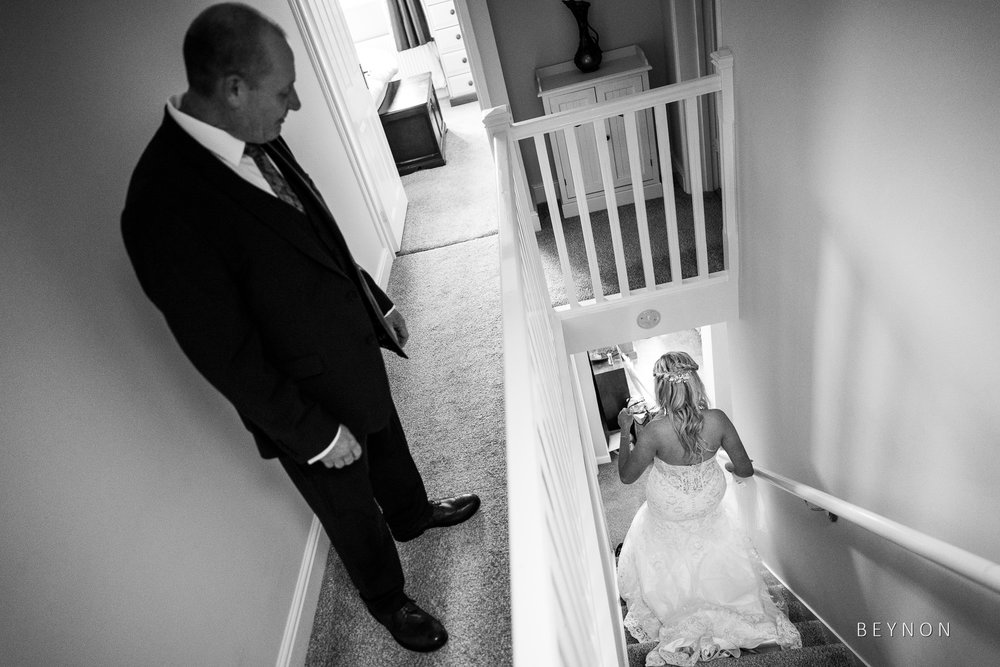 Dad watches his daughter walk down stairs in wedding dress