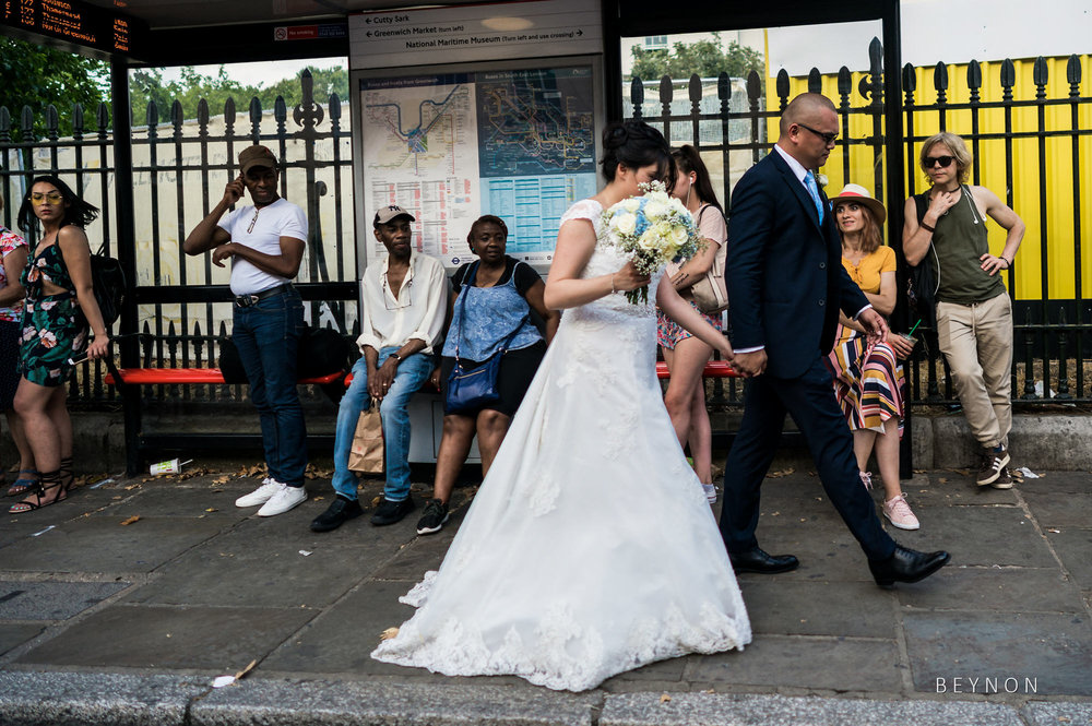 The married couple walk pass people at a bus stop