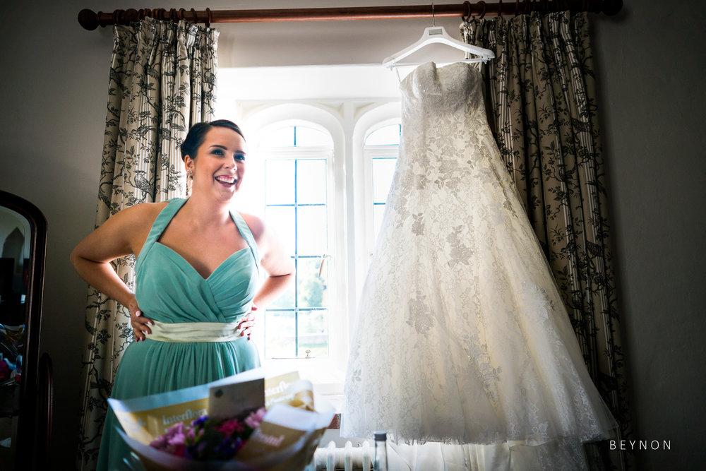 Bridesmaid stands next to wedding dress
