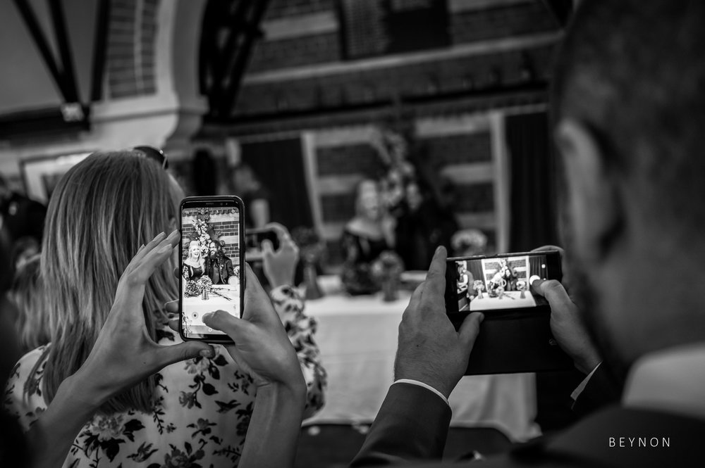 Guest uses their phones to photograph the newly weds