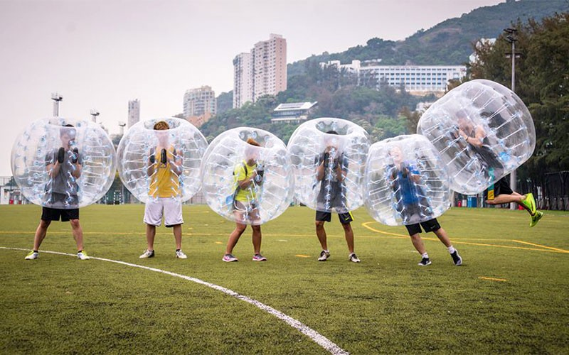 6 players in bubble suits lined up with the one on the right end jumping into the line of players
