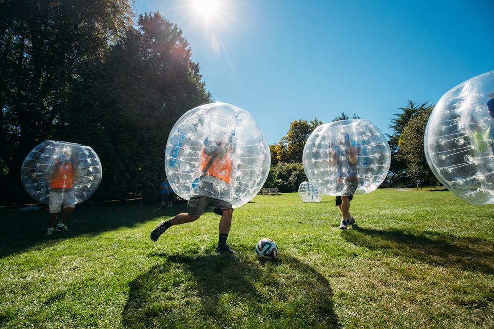 Bubble soccer players playing a game.  One player goes to kick the ball while 2 players play defense