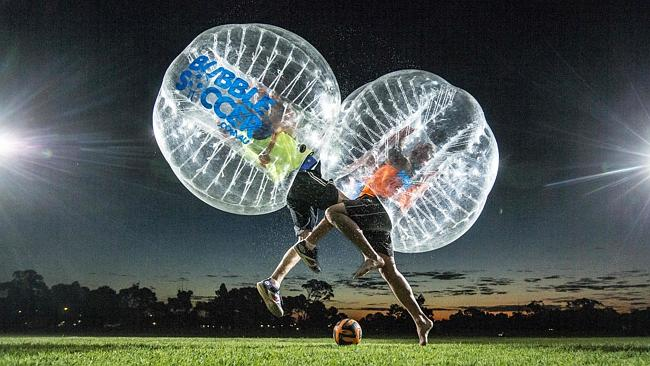 2 bubble soccer players collide in mid air with the soccer ball right below them