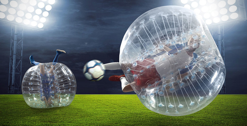 man in bubble soccer suit diving while shooting the soccer ball.  Other team player is upside down in his bubble suit