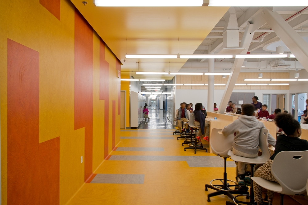 Environmentally-friendly and naturally anti-bacterial linoleum is deployed on both floors and walls to bring color to the commons area in each classroom cluster.
