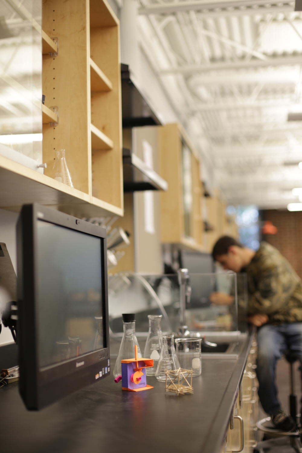 Each lab station features a die-cutter, a 3D printer with direct exhaust, and an arm-mounted video monitor.