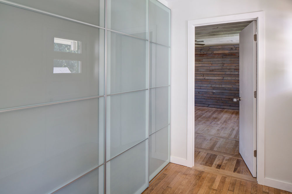 Rolling glass panels conceal the laundry area and coat closet.