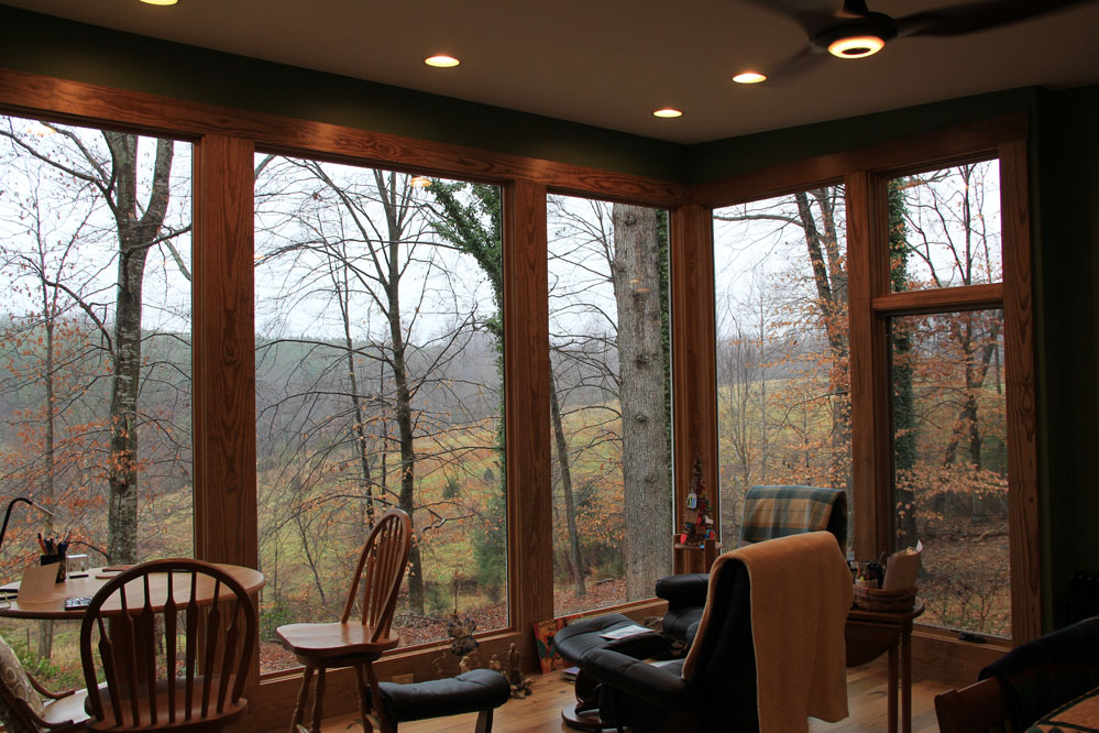 The bedroom sitting area offers tranquil views through the forest to nearby fields and ridgelines