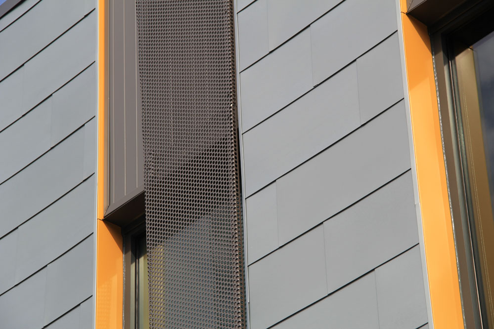 Perforated steel sunshades animate openings in the south-facing office block.
