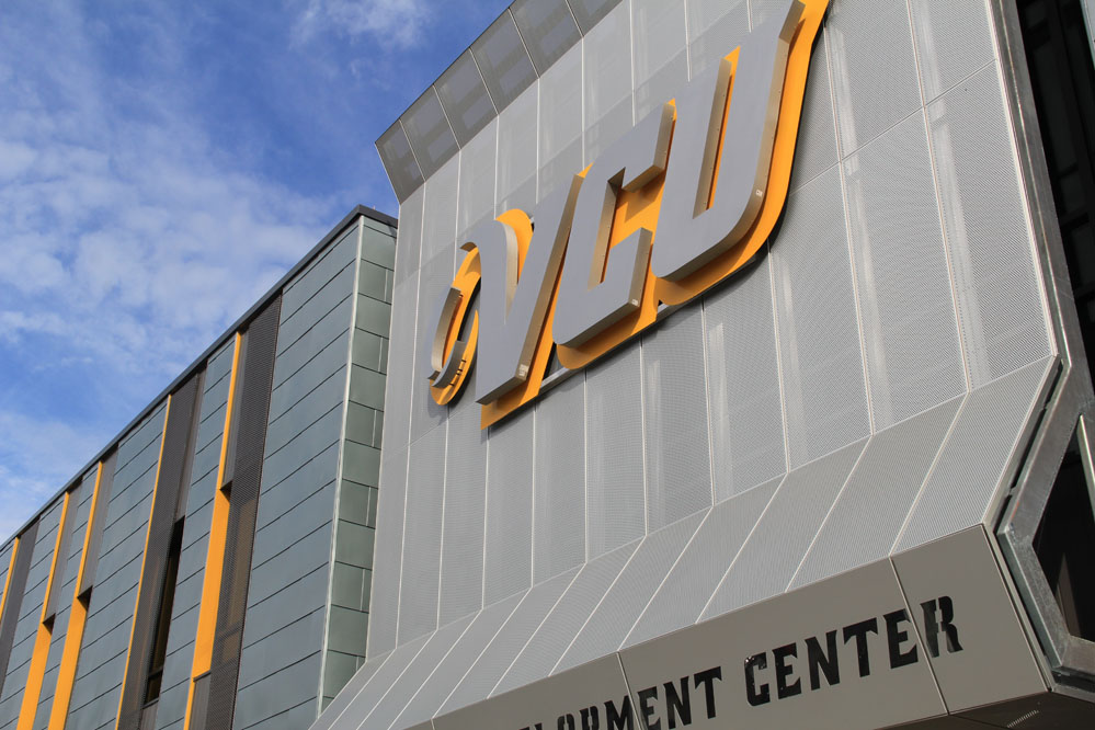 A perforated aluminum screen, highlighted by the VCU logo, shades the south-facing glass of the lobby.