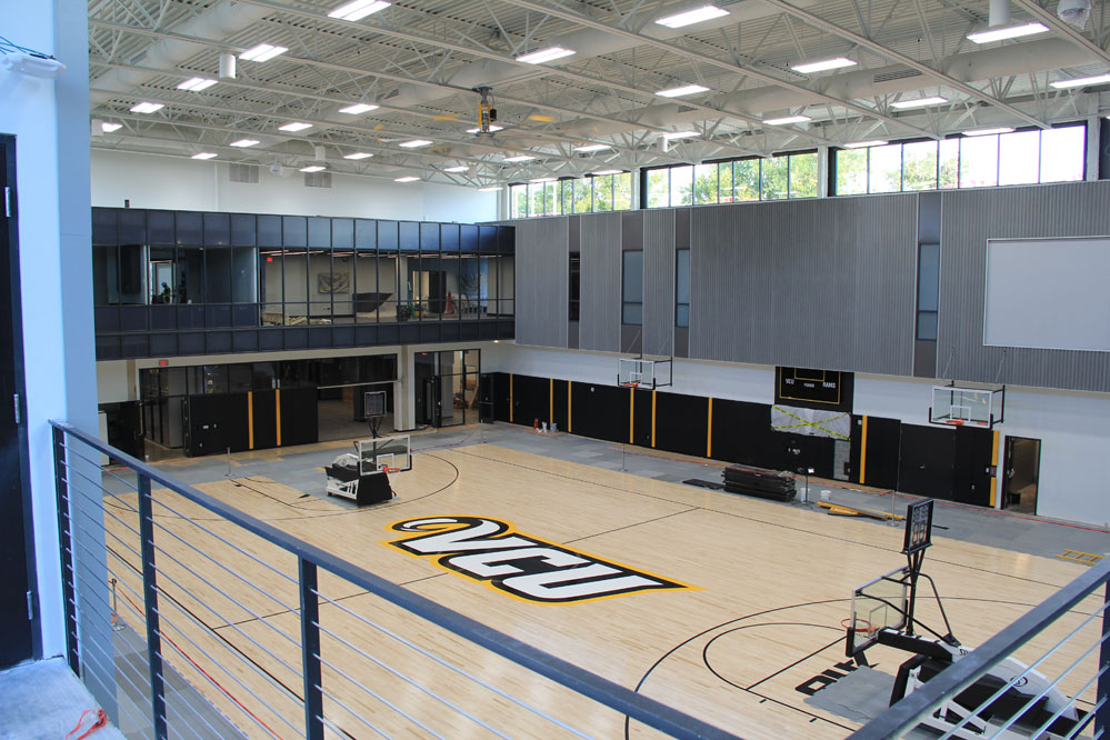 Locker rooms, lounges & offices enjoy views to practice gyms below. Acoustical metal roof deck & wall panels ensure speech intelligibility in the gyms. Gym floors feature FSC-certified maple flooring