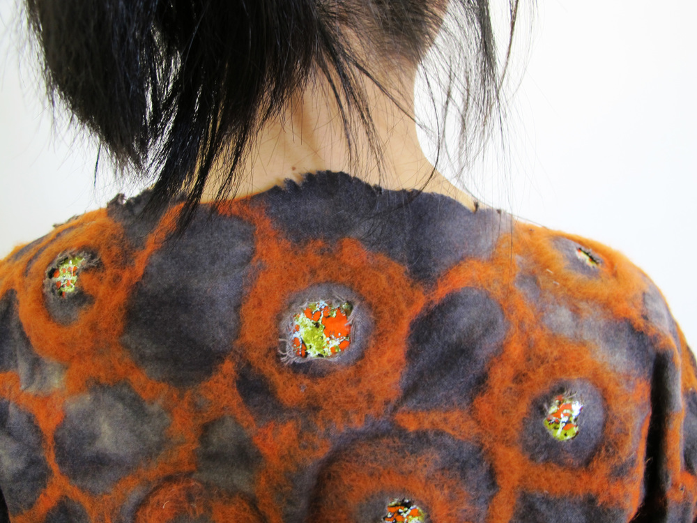 Dyed wool garment with needle-felted wool and enamel pieces.