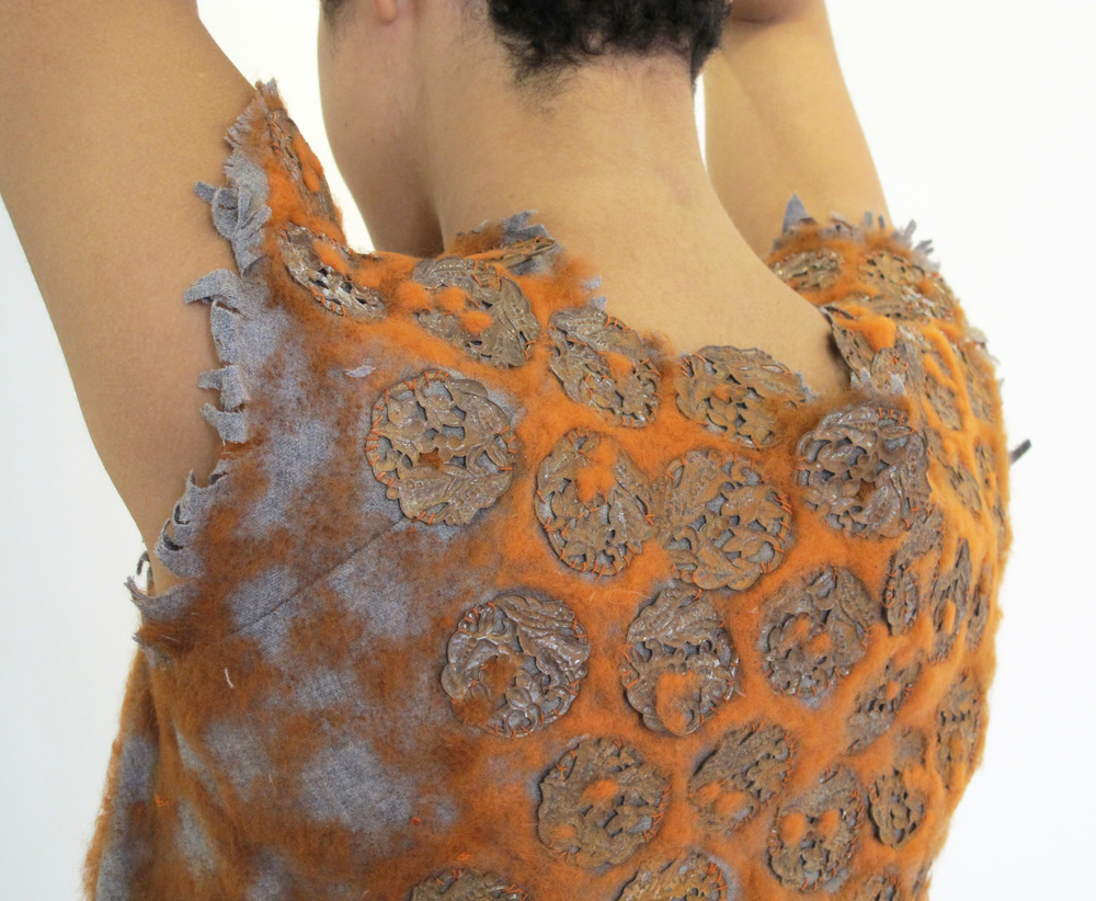 Wool garment with needle-felted wool and rusted metal pieces.