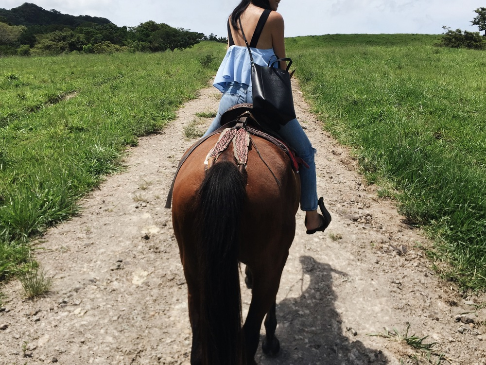 Horseback riding in Borinquen,  Costa Rica.  ZARA  Top  / CITIZENS OF HUMANITY   Jeans   / CÉLINE   Bag
