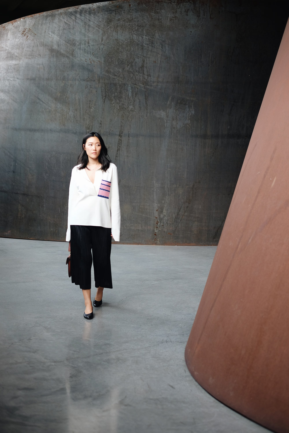 CÉLINE Top / ISSEY MIYAKE Pants / J.W. ANDERSON Bag / MARI GIUDICELLI Shoes (More here)