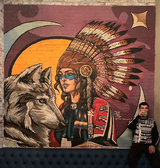 """Native"" Acrylic on brick 14' x 16' @blacksmithsdtla  Excited to add a couple pieces to the downtown area. The bar resides close to ""Indian alley"" a historical landmark here in downtown.  #indianalley #indianalleyart #dtlamurals #dtla #nativeportrait #nativeamericanmural #nativeamericanart #femaleportrait #crescentmoon #risingsun #wolfportrait #wolfmural #headdress #purpleart"
