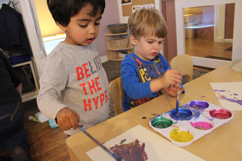 """Sanjay said, """"It's a rainbow!"""" after he dipped his brush into all of the colors. Then Hamish said, """"I'm making a rainbow,"""" and created an arc on his paper to demonstrate his knowledge about the shape of rainbows."""
