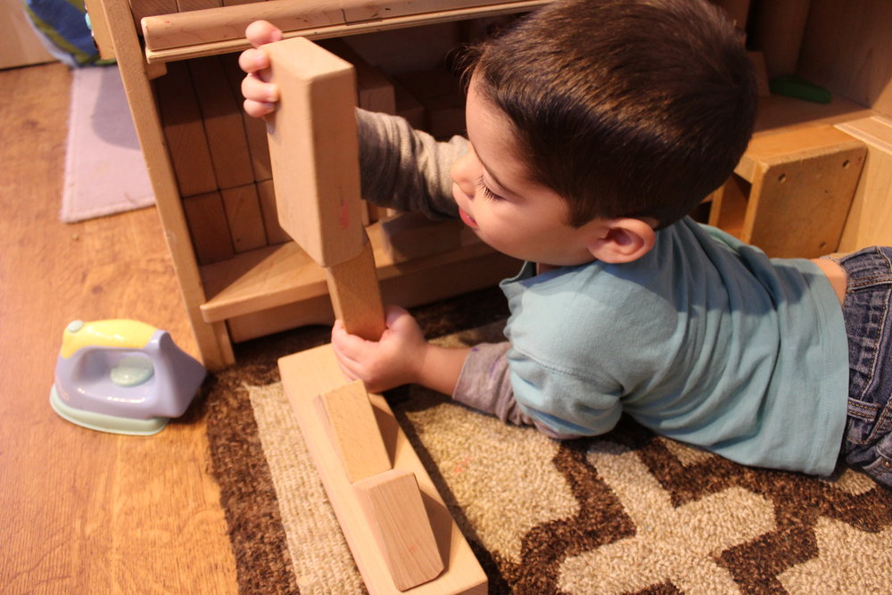Dylan carefully stacks the blocks with his friends on them.