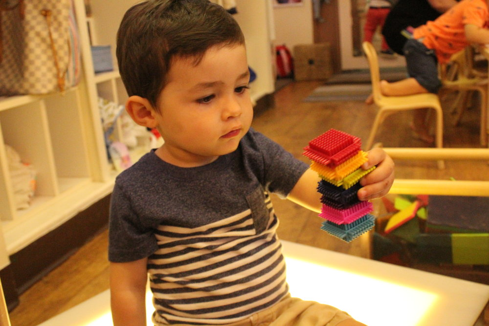 Emilio is always stacking and building. He likes to line up all of the cars or trains. He likes to build tall things. He also loves to be near his friends and to comfort them with their pacifiers if they need it!