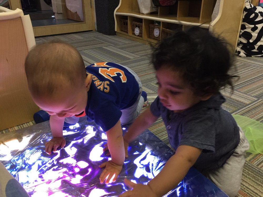 Leo and Rohan loved the texture of the warm, puddles of bright paint on the light table! The students used their whole bodies to explore this provocation. The children pressed their hands, feet and tummies into the paint, smearing the paint across the illuminated light.