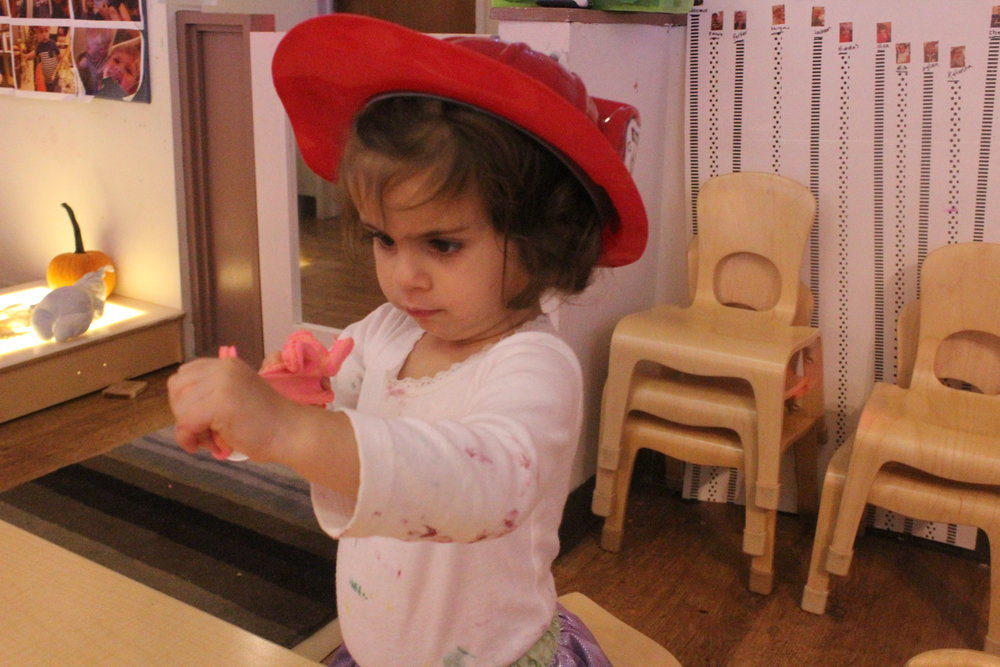 "Lately, Nina has really enjoyed exploring dramatic play and all of the sartorial items that go along with it! In this photo Nina is putting a ""fire out!""."