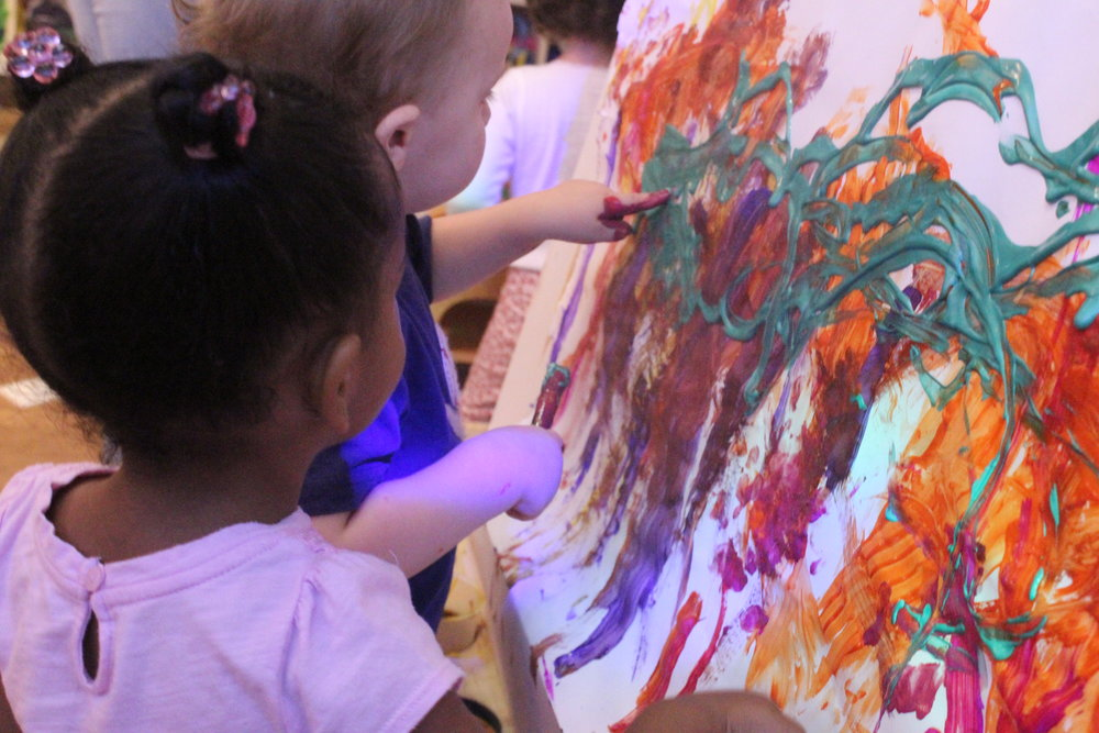 """The children have taken a keen interest in working alongside one another at the easel. The easel is a great tool in fostering language development - while standing side by side it gives them an opportunity to begin conversations with one another. Here are some quotes!  """"More!""""  """"Green!""""  """"Wow!""""  """"A,b,c,d,e,f,g,...!"""""""
