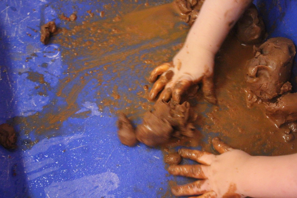 """We continued our exploration of clay with water and allowed only allowed the children to use forks with the materials. This really lets them strengthen their fine motor skills.  """"Wet!""""  """"Ahhh!""""  """"Brown!""""  """"Hahahaha"""""""