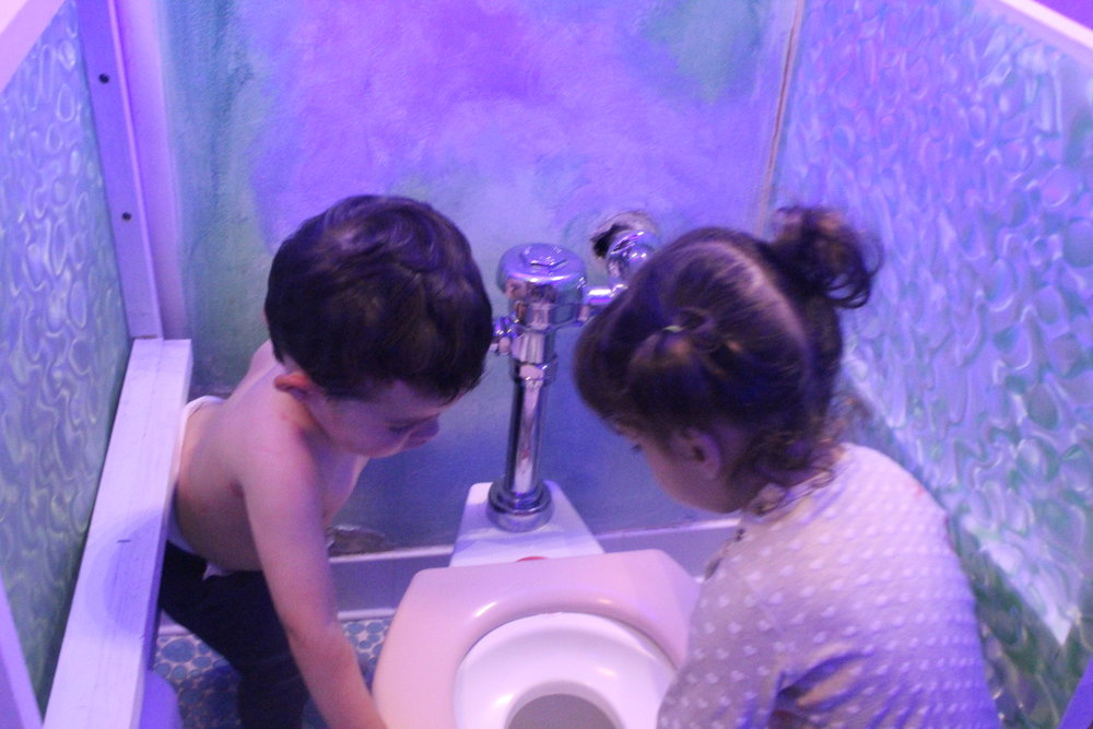 """Currently, part of 2A's identity is shifting from toddlerhood to being """"big kids"""". We're seeing this shift take place in a strong interest in the potty.  """"Woah!""""  """"Potty go flush!""""  """"More!""""  """"Pee pee go there?"""""""