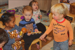 Nicholas passing out instruments at circle time