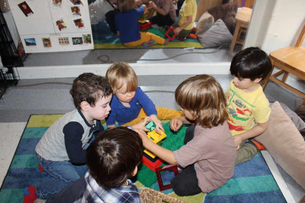 Harry appeared interested as he observes the children exploring and building together.  He joins the group and seems comfortable as he engages with them.  It was amazing to see how the older children and Harry shared the space and took turns building.