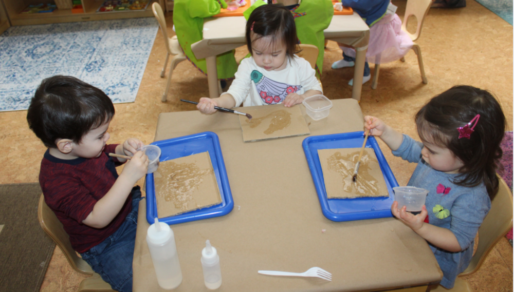 This is a 3 step project they first applied or poured the glue on the cardboard piece, and spread the glue using a paintbrush.  Using brown and white crinkle cut shredded paper, the children placed them in different areas on the cardboard.  The cardboard piece is air dried for a day before going to the next step, painting.