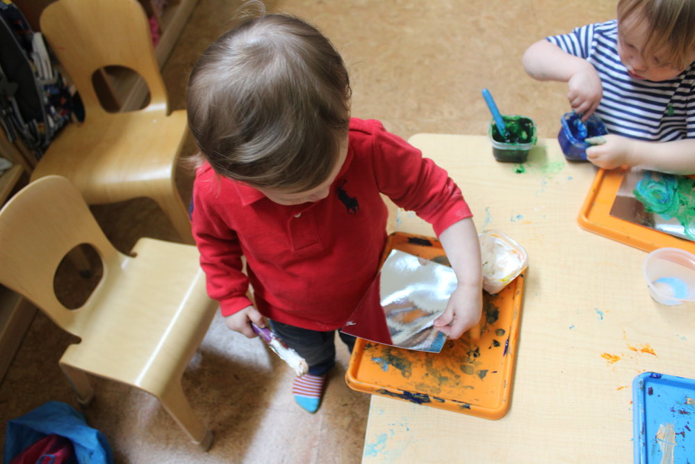 The children were exploring mirror painting at one of the tables.  Grayson observed until he picked up a paintbrush and mirror paper.  It appears that the mirror paper stimulated his curiosity and interests, even though he did not engage with the materials.     Grayson is one of our recent students that joined classroom 1B.  He is gradually adjusting to the classroom environment, routines, schedules, teachers, peers, and activities.  It is always a difficult transition from home to school for young toddlers.   As teachers, it is essential to provide opportunities for them to explore and discover things at their own pace.