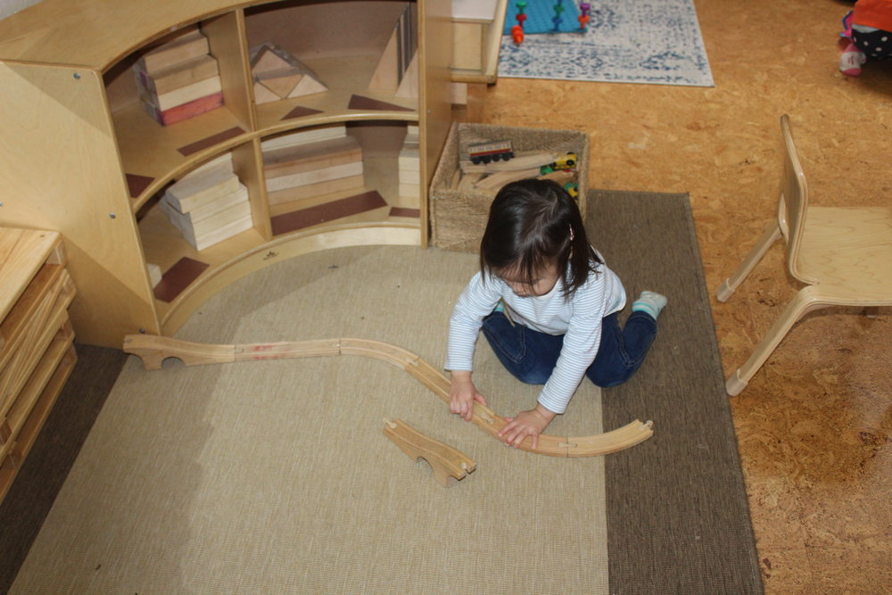 Playing with toys is an essential part of a child's development.  The railroad system can provide an excellent stimulus for creative play.  Train tracks are innovative; they promote problem-solving, imagination, language, socialization, and fine motor skills.   Straight, curve and bridge style tracks help children to put train tracks together and put them in different ways.   Each piece stimulates Edith's imagination and creativity.  It also enhances problem-solving skills.   Edith created her track configuration.  She carefully chose and connected each track, and each time she interacts with the tracks, she is extending them further.  She observed and focused on each track, making sure it fits.