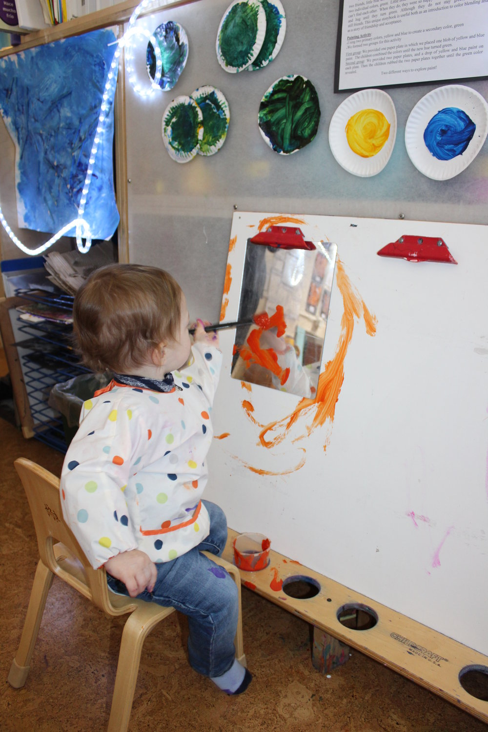 Grayson is feeling at ease in his classroom environment and interacting with different materials.       This fun activity helps children to experience a different form of painting on paper. It allows them to explore, experiment and discover that the composition of paint appears differently on each surface they paint on.  Mirror paper makes the painting shimmer, and the metallic surface creates a shiny and slippery appearance.  Each child projected different strokes on the mirror using paintbrushes.  As they see their reflection, they also see the different strokes he/she has painted.