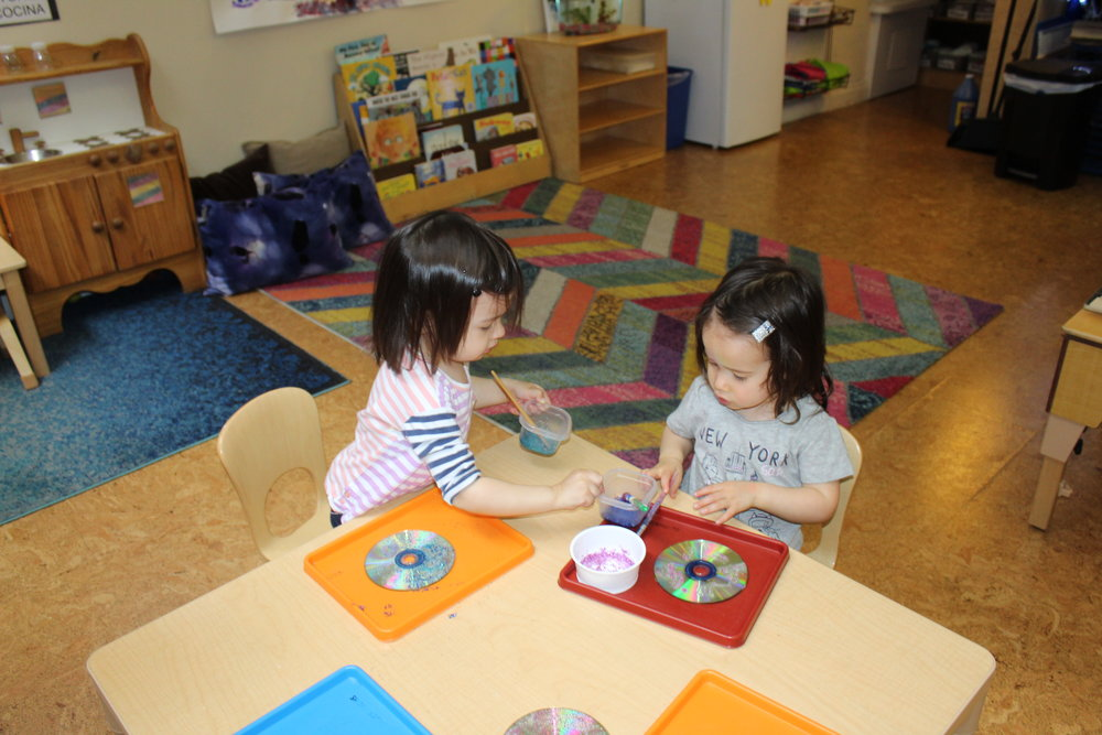 Some children were creating suncatchers by adorning CDs.  They used glitter, glue, and sequins. Each step enhances their cognitive ability, as they think about their choices.  They selected two different colors of glitter and mixed each with glue.  Then they spread the glue on the CD, promoting fine motor development as they maneuver their hands, back and forth.  The children will continue their activity on Artsy Day, Thursday.   Each child would have the opportunity to create and explore making a suncatcher.