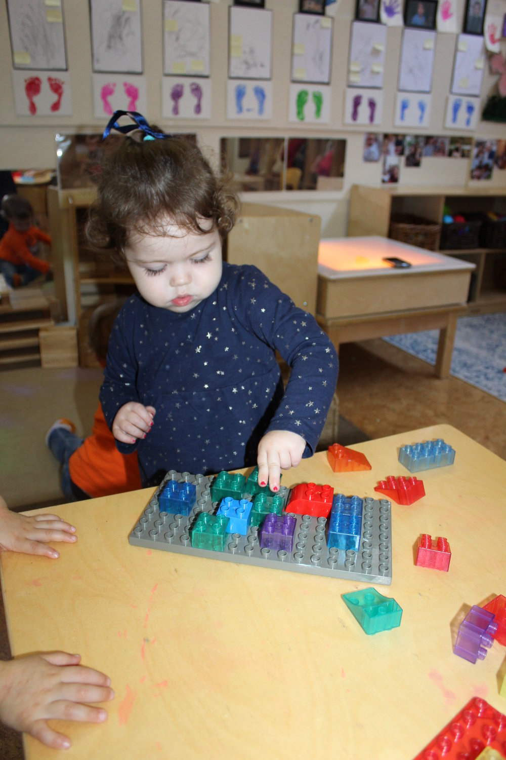 The Lego blocks and plates displayed on the table, Edie observed and interacted with them.   She pressed one square shape onto the Lego plate and continued selecting different color squares unto the plate until it is almost complete. Experimenting and investigating each piece she chooses and rotates to design, helps her create her structure.