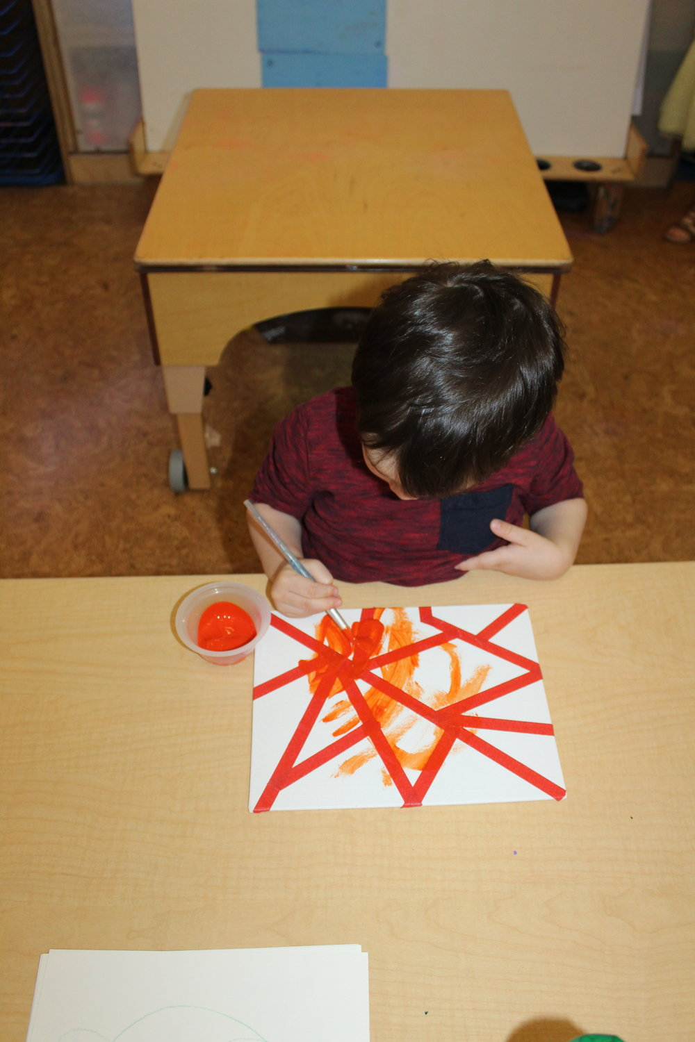 Using green, yellow, and orange hues, tape, and a rectangle shape canvas will make an art piece intriguing. The children appeared interested and amazed, as they observed the abstract design that was created by using different tools and materials.