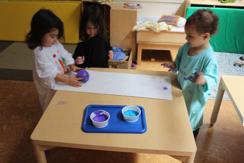 Painting with balls creates a different kind of texture on paper, as the children roll the ball back and forth. They are learning about color, texture, and creating art.