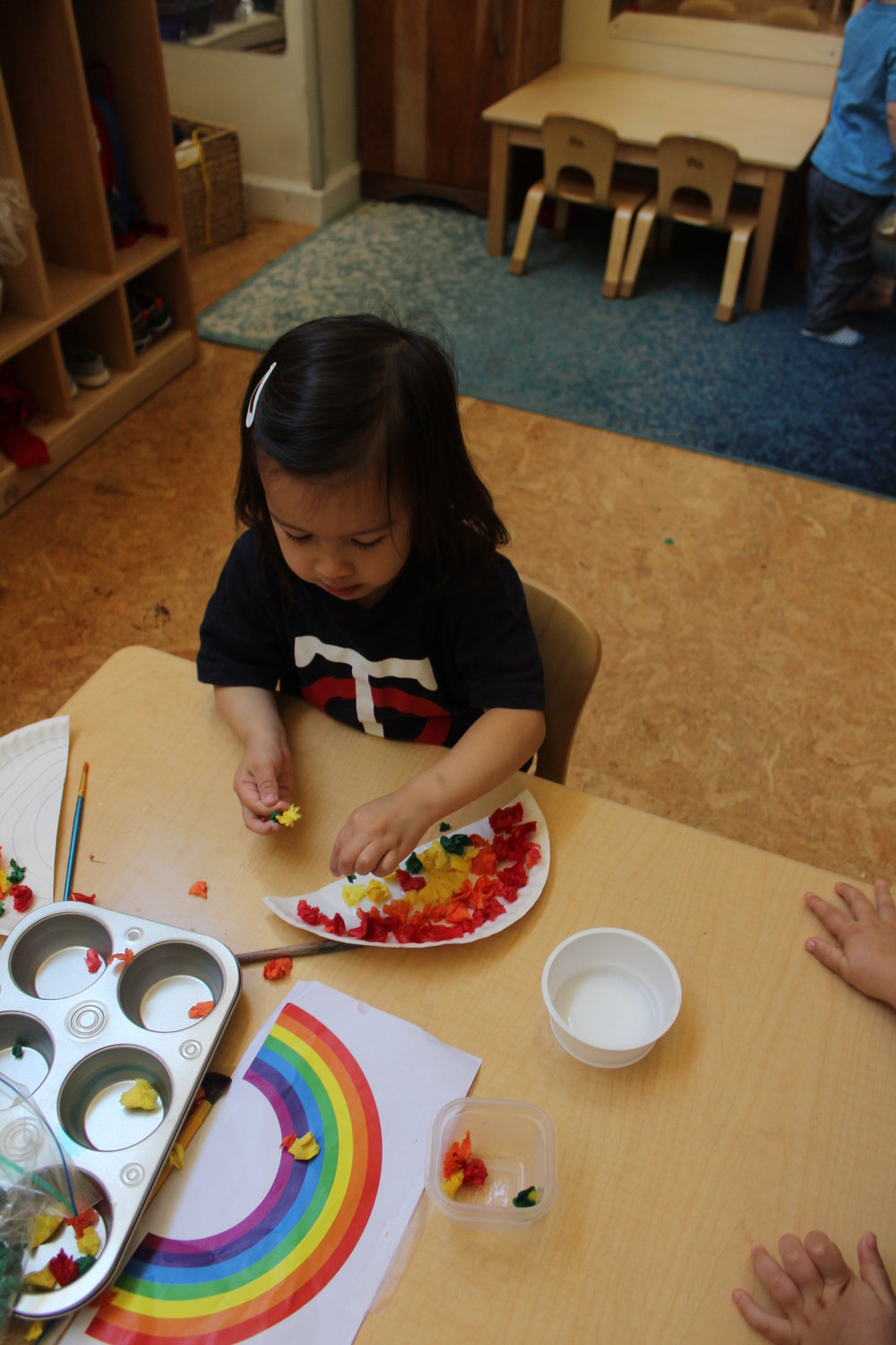 Creating a rainbow using paper plates and tissue paper!
