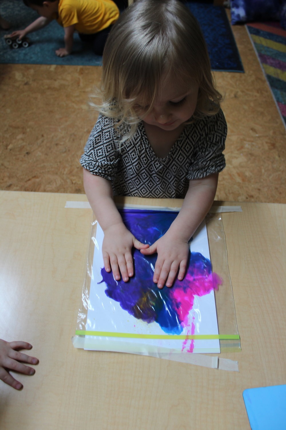 Ziploc painting is a color, sensory, imagination, and fine motor skills all in one fun activity.   Fine motor skills are those that require the ability to use and coordinate small muscle groups.   Giving children opportunities to play with different types of textures and objects helps them to build new ways of talking about the world and building language.  This type of sensory play is also calming for children. It helps regulate their internal discomfort, whether that discomfort is restlessness or some other type of agitation.