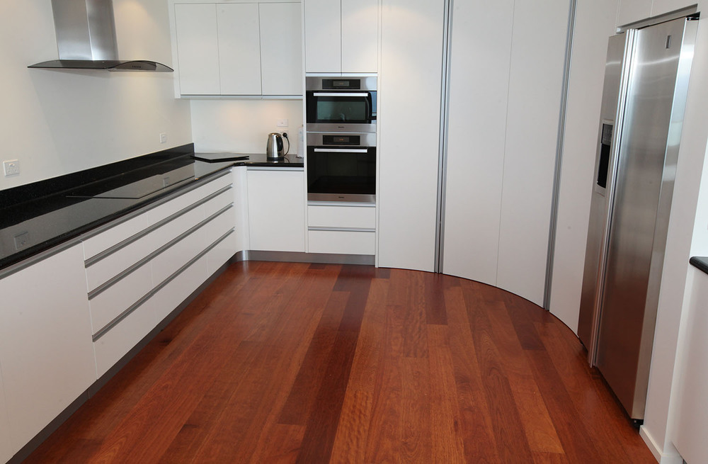 Laquered kitchen showing full height pantry doors