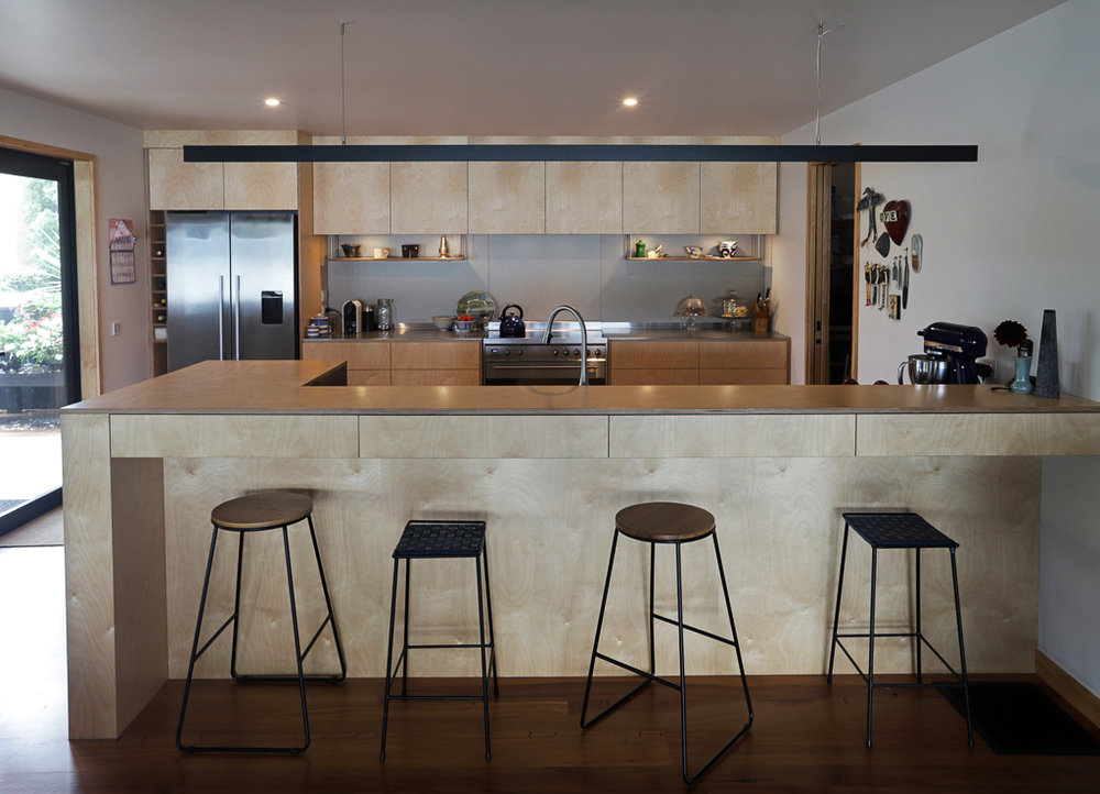Contemporary kitchen with oiled birch plywood and plate stainless steel benchtops