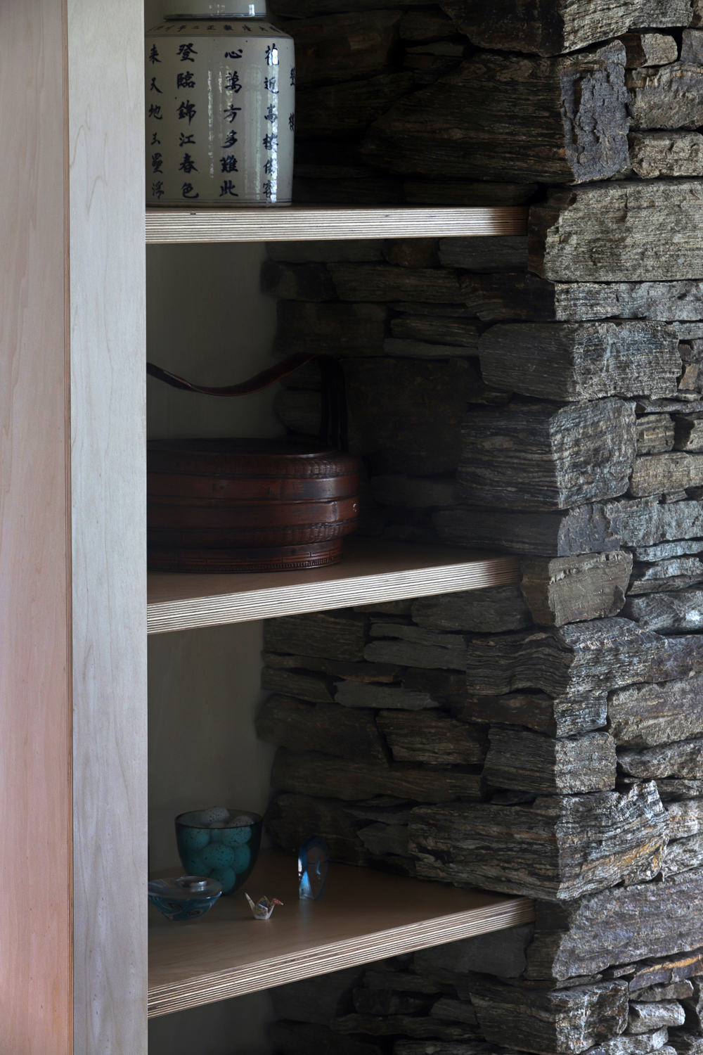 In-built shelving to rock-walled fireplace