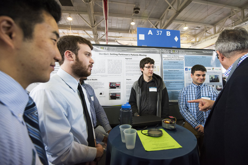 Northeastern UniversitySchool of Engineering  - Under the leadership of Professor Waleed Melesis's Enabling Engineering Capstone Senior project a group of six senior engineering students developed a hip mounted StartGait prototype for visual cueing based on predictive gait algorithms.  The team leader, Justin Schwartzseid is pictured here presenting the prototype to judges at the 2017 RISE showcase.