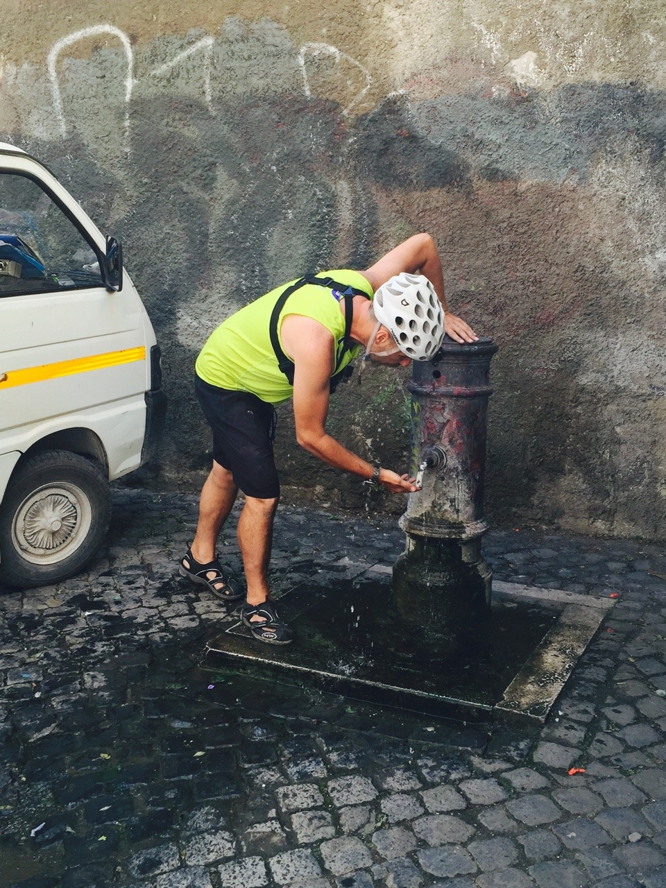 Our bike tour guide, Emmanuele, showing us how to drink water from a Roman fountain.