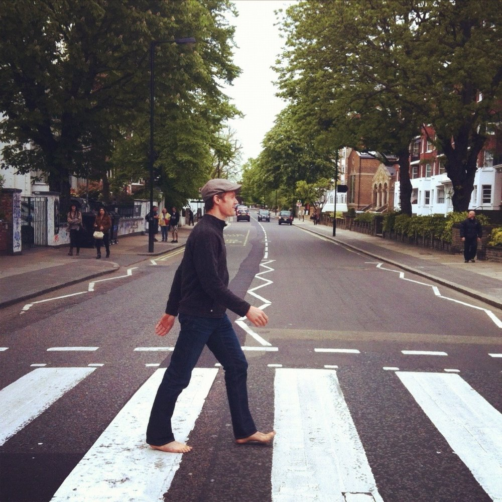 """Abbey Road     Going to Abbey Road to visit the infamous crossing was a pretty cool experience. To get there, just get off at  St. John's Wood  Underground Station and it's less than five minutes' walk before you come around the corner to find all the other keen Beatles fans. Traffic flows regularly so everyone who's come for their own picture crossing the road sneaks out into the middle of the road before the next car comes along. People from all parts of the world come to marvel at a crosswalk, respectfully taking turns with each other to get that """"right"""" photo. Frances got mine in the second of three attempts. For extra fun I went barefoot like Paul ;) Though some might scoff at the idea of visiting such a place in all of what London has to offer, I can attest that it was way  more fun than any museum I've ever been to!   For reference, here's Iain Macmillan's original for the Beatles' Abbey Road album cover .It's also interesting to see the alternative photos  taken on the same day."""