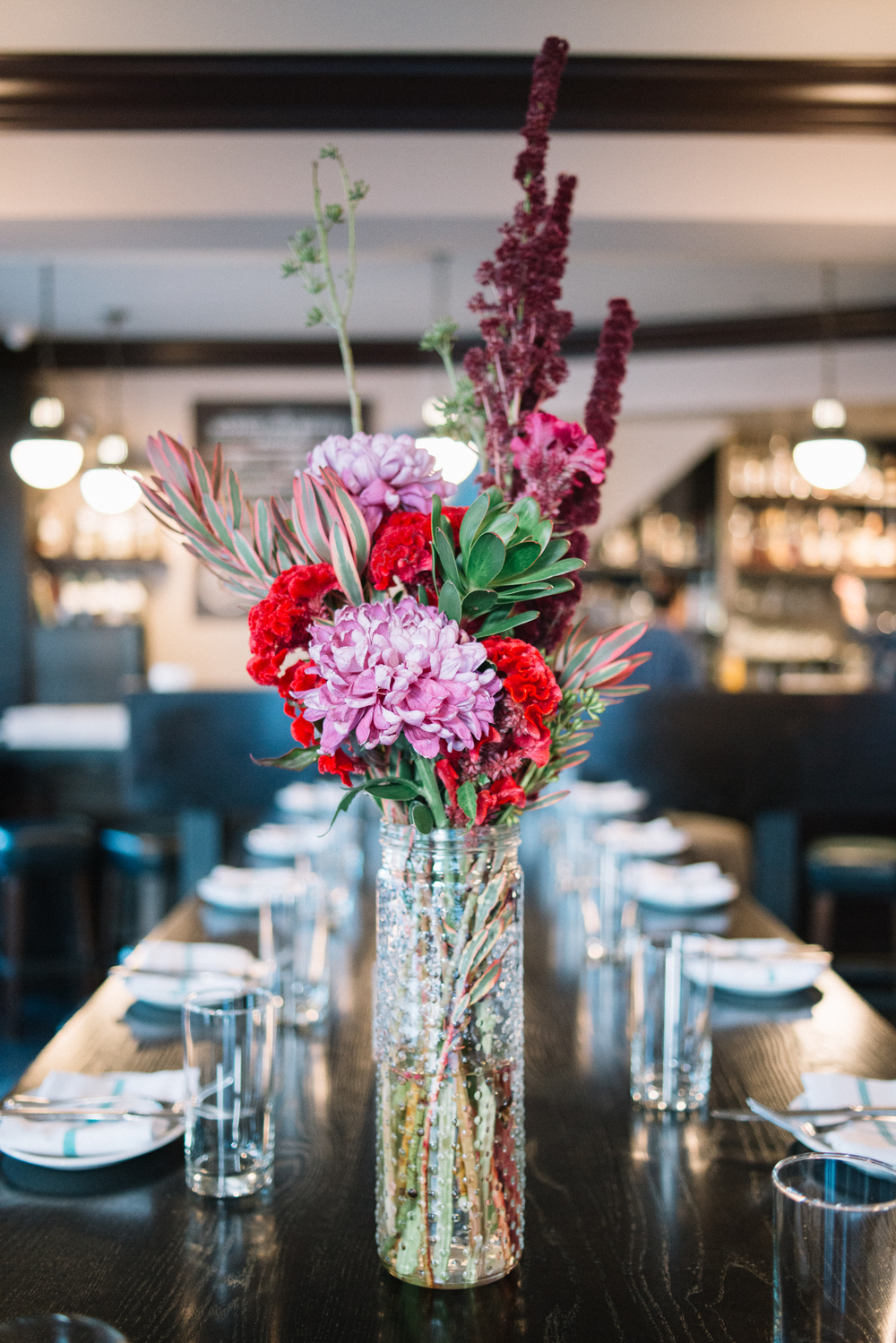 red+flower+arrangement+in+clear+vase+on+a+business+table.jpeg