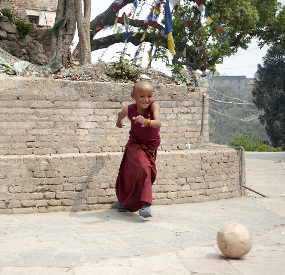 Young monk in training having an impromptu game of soccer, Kathmandu