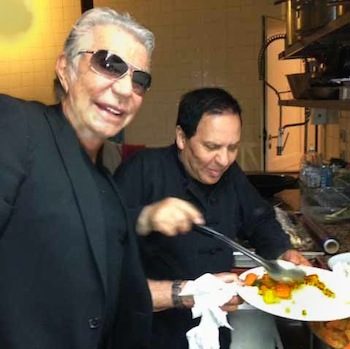Two masterminds, Roberto Cavalli and Azzedine Alaia, are photographed together cooking couscous.