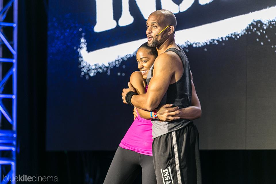Christine Iloni  on stage with Insanity Coach,  Shaun T